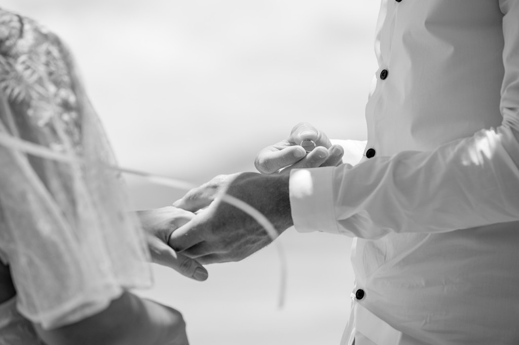 Monochrome closeup of groom slipping the silver ring onto his bride