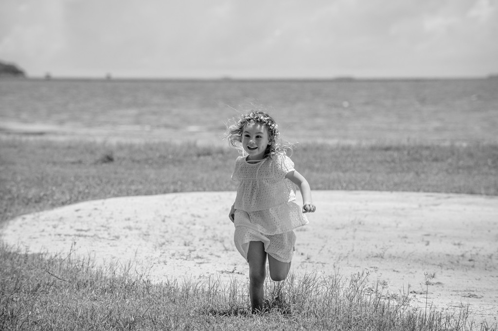 Monochrome of the energetic flowergirl running through a flower medow