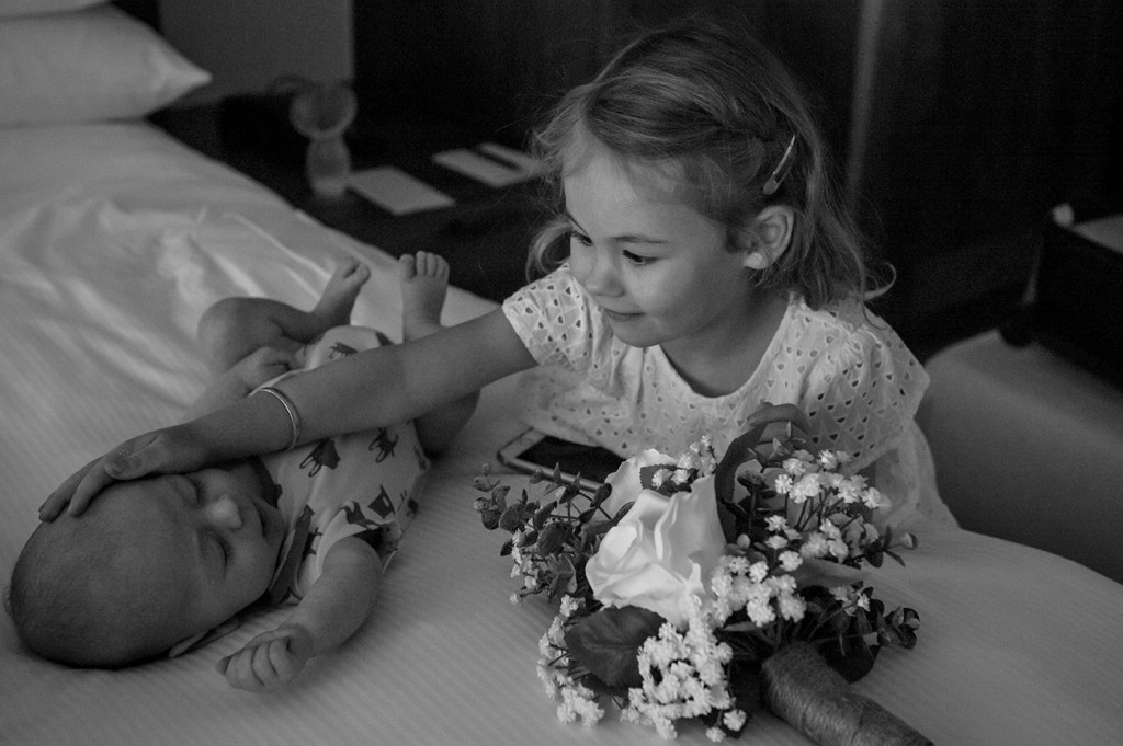 Adorable flower girl playing with her baby brother
