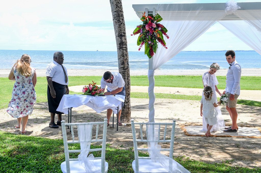 Wedding guest and witness signs marriage certificate at destination beach wedding