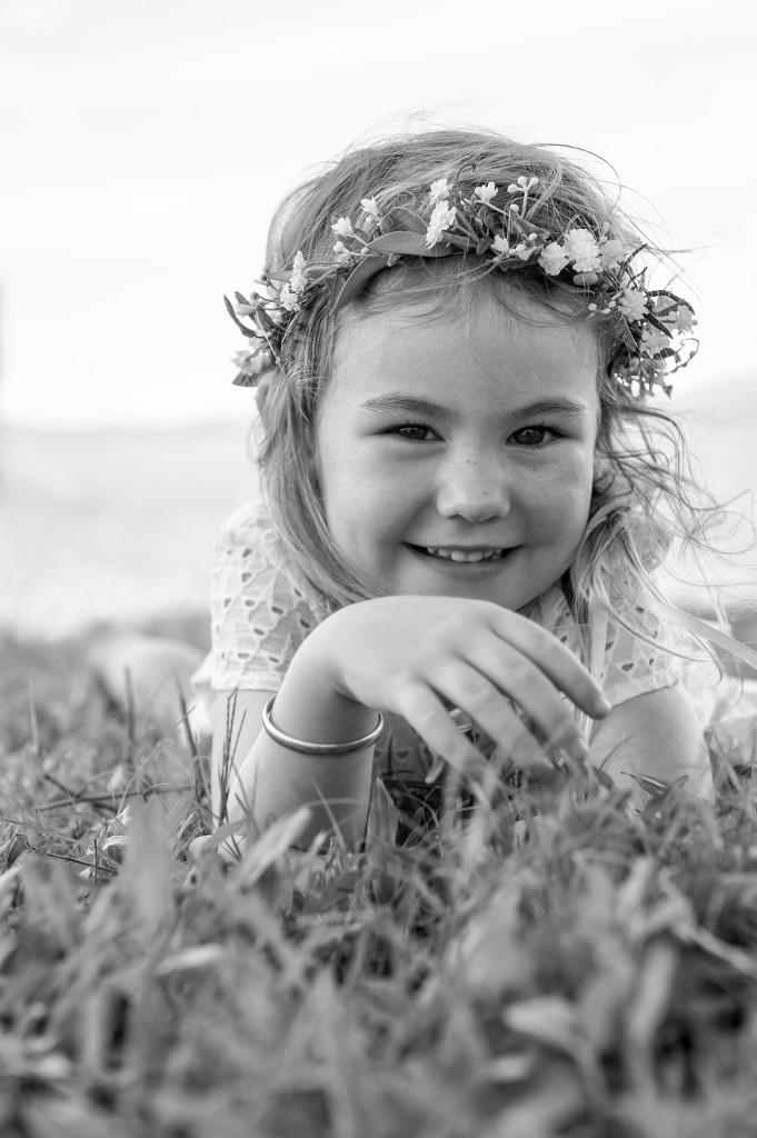 Monochrome of sweet flowergirl smiling into the camera