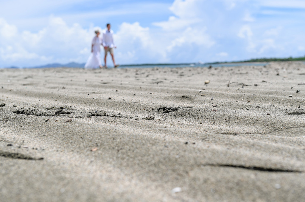 Soft focus of the newly married couple strolling on the black sand beach