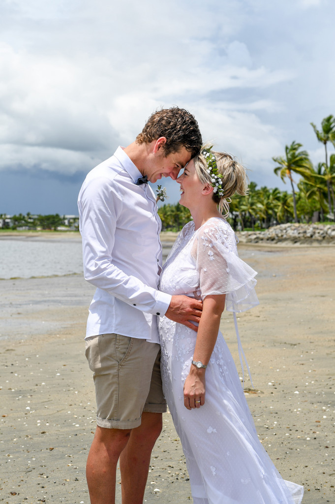 Bride and groom look into each other's eyes at the Magnificent black sand beach Fiji