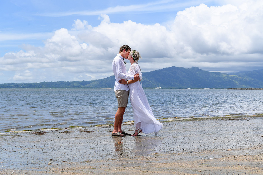 The newly married couple kisses while standing in the awe-inspiring Pacific ocean at their destination wedding
