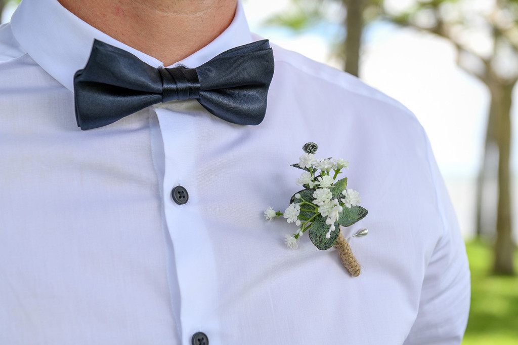 Closeup of Black velvet bowtie and white flower boutonniere