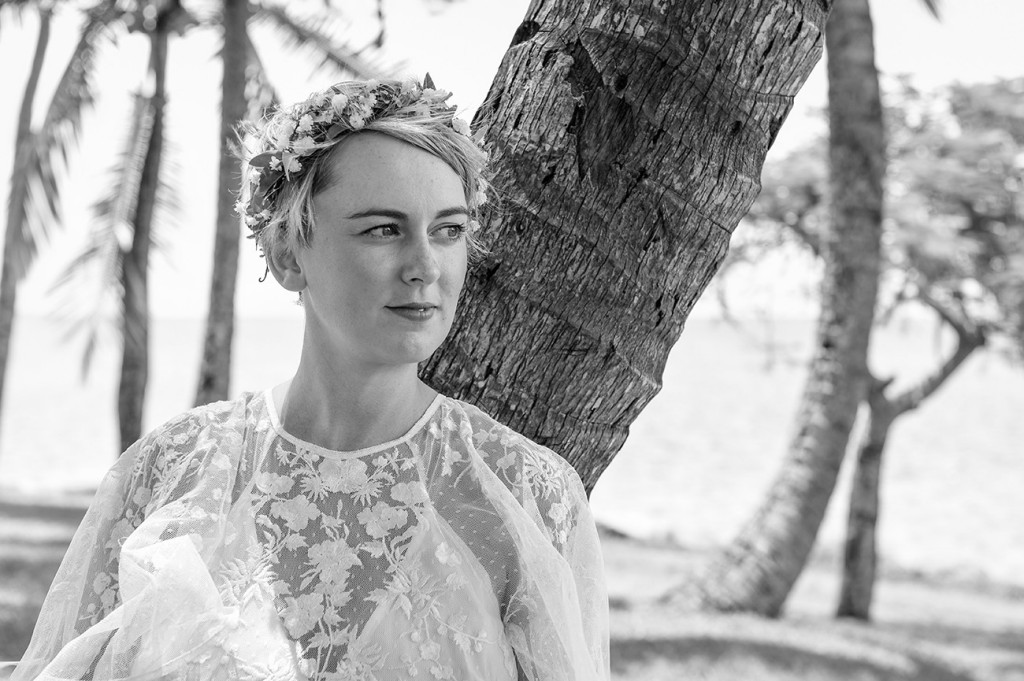 Monochrome of the stunning bride leaning against a palm tree