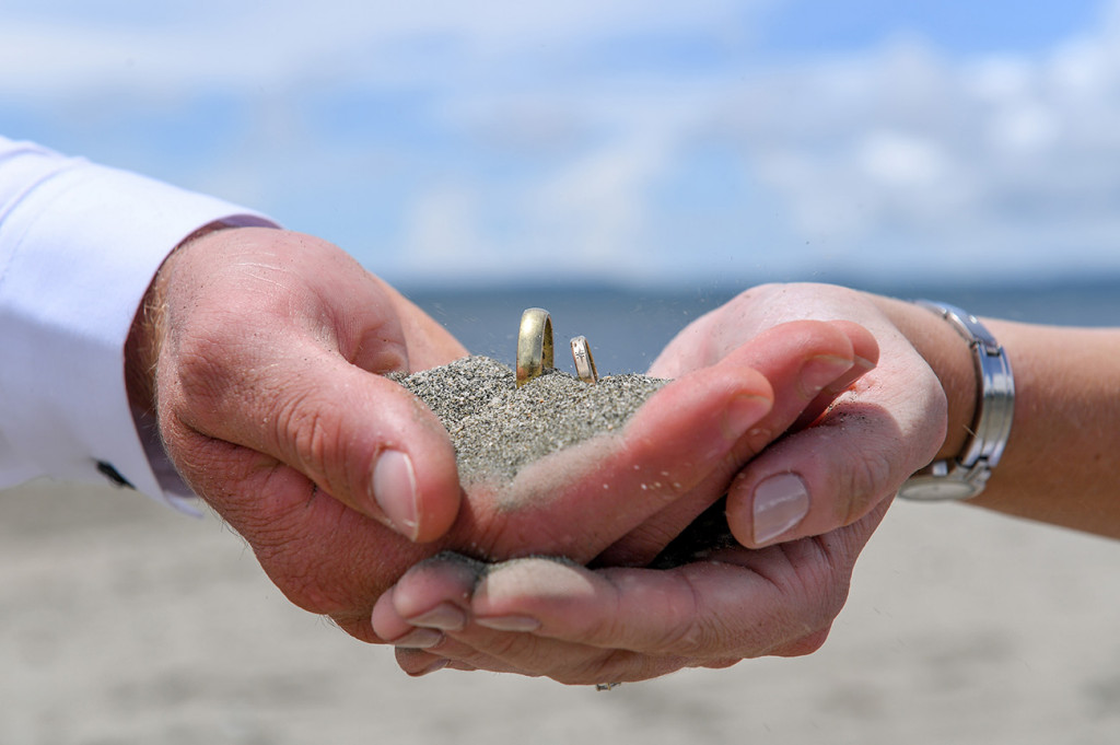 Bride and groom cup their gold rings in black sand