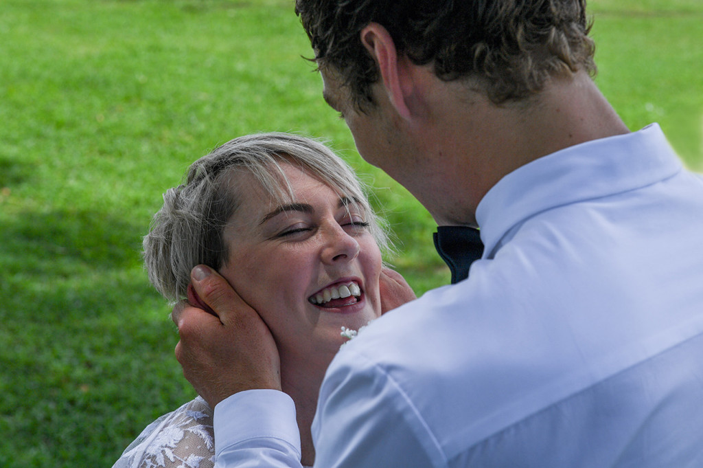 The bride laughs as the groom cups her face in his hands