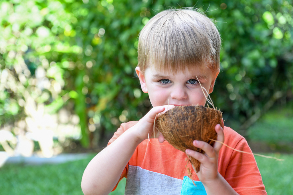 Cute baby boy eating from coconut shell