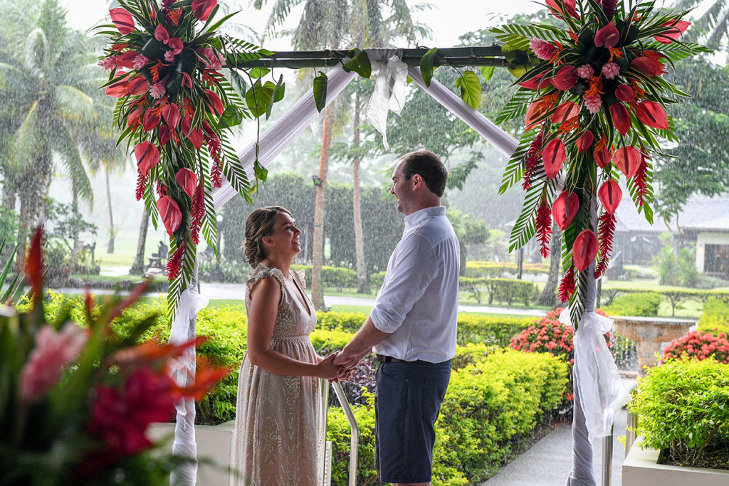 Bride and groom laugh at the tropical red flower altar