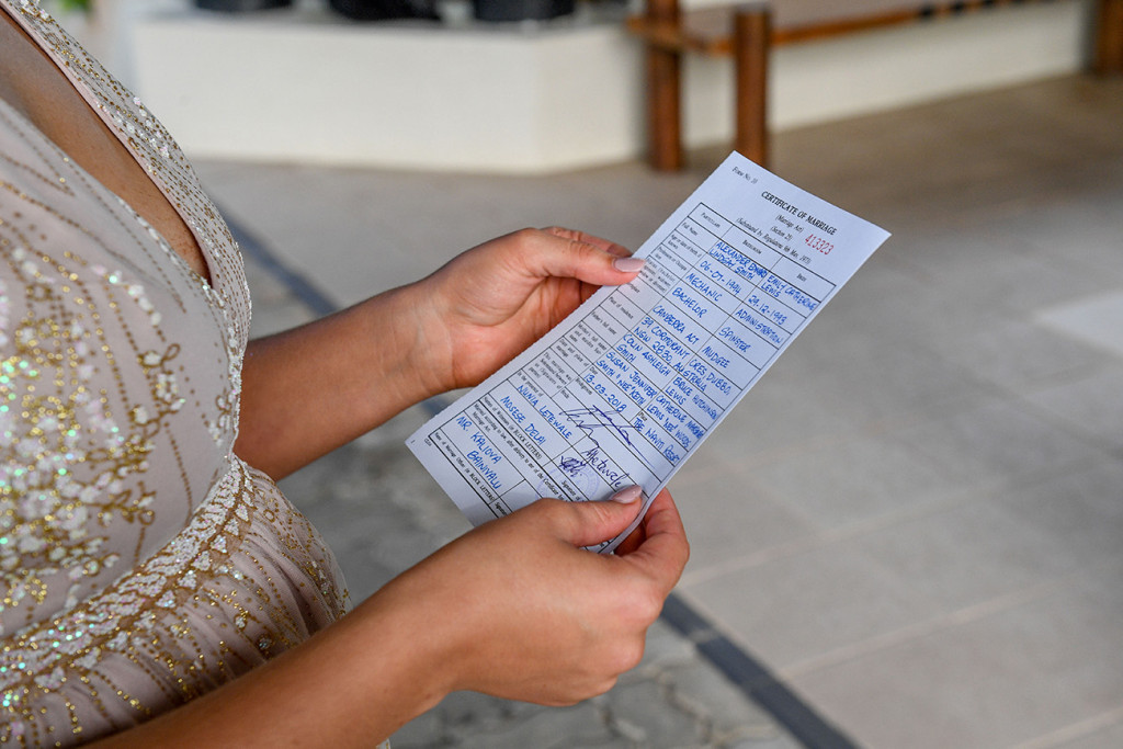 The bride holds up her wedding certificate