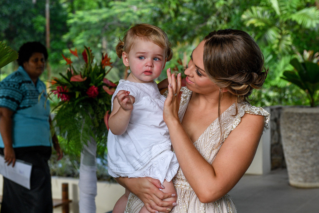 Bride wipes her cute daughter's tears at the wedding