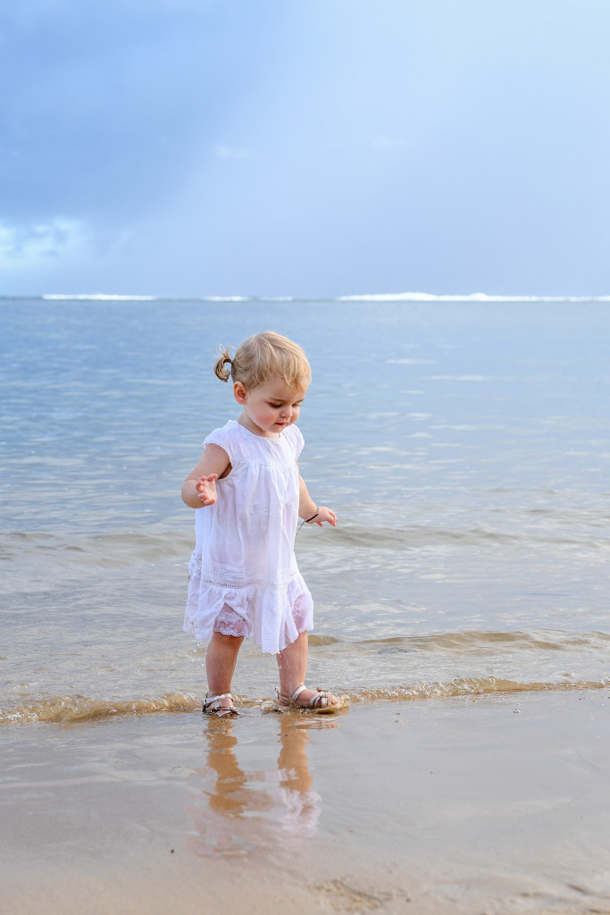 Cute baby girl stumbling in the ocean