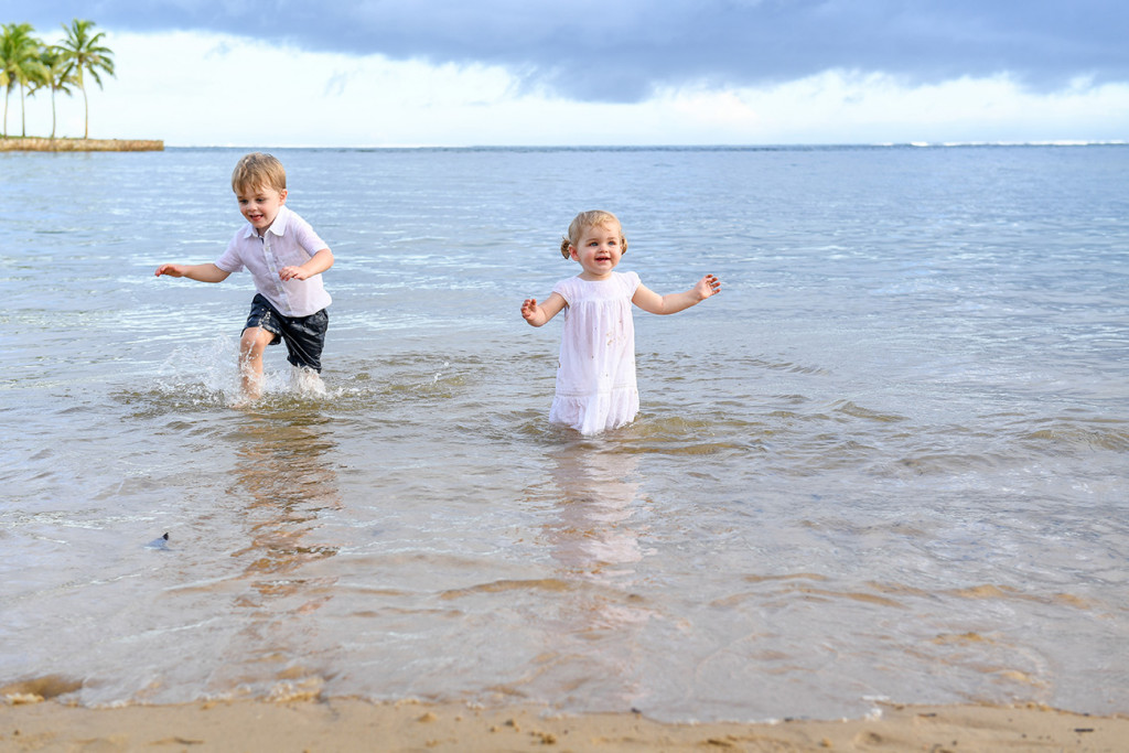Cute baby brother and sister playing in the Pacific Ocean at Fiji