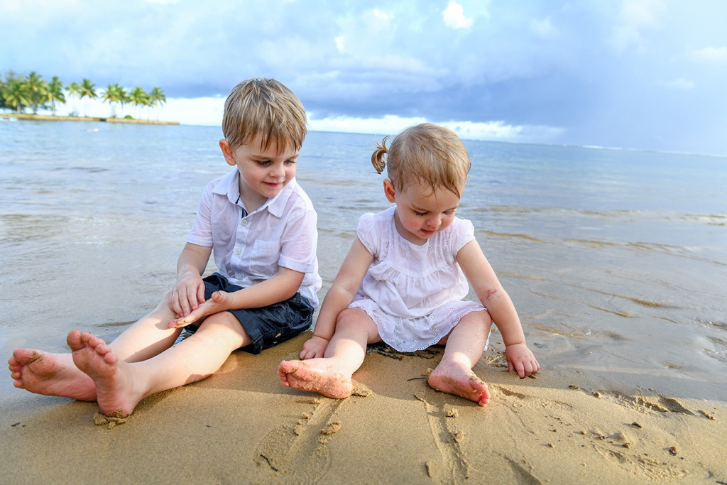Cute baby brother an sister drawing in the sand by the beach
