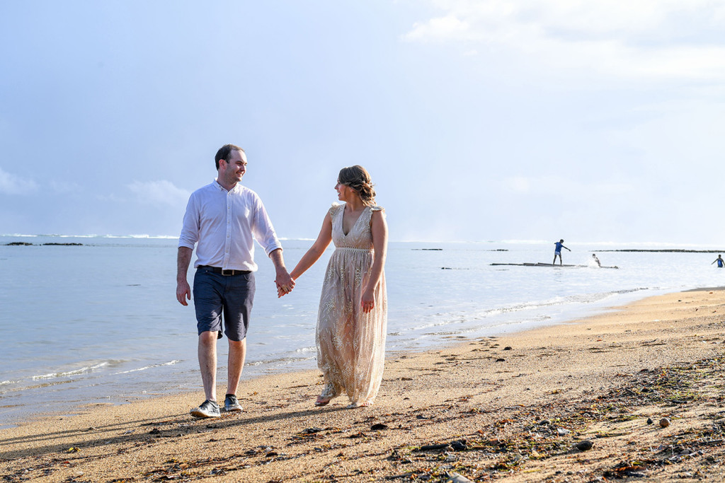 Bride and groom stroll hand in hand by the beach