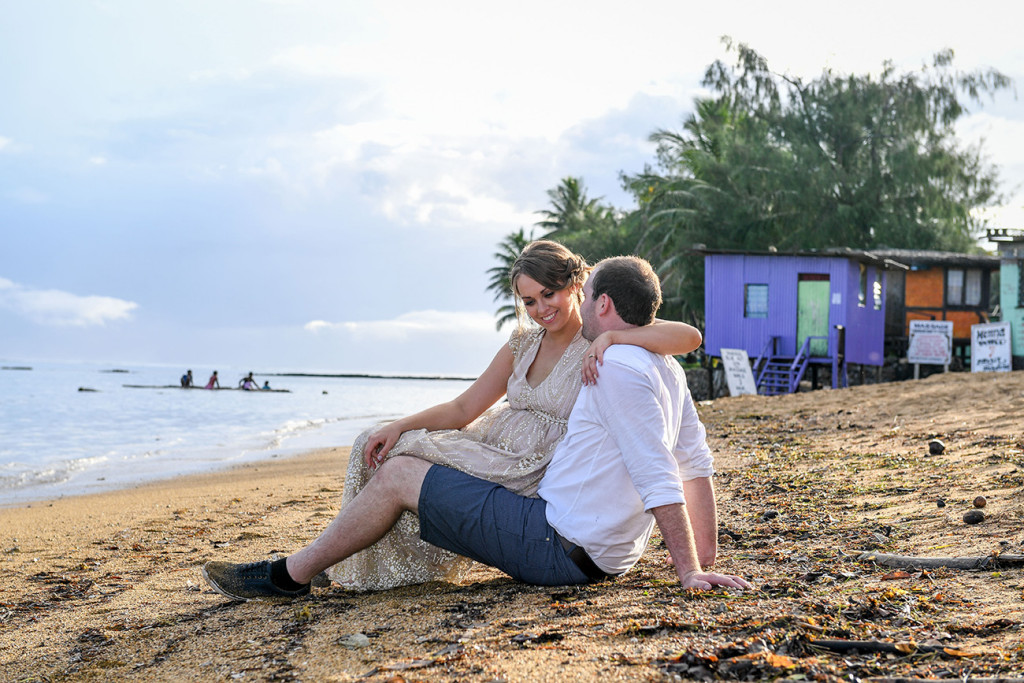 Bride sits in the grooms lap on the beach at Naviti Fiji