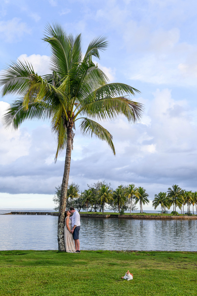 Bride and groom stand against a palm tree at the breathtaking beach of Naviti Fiji