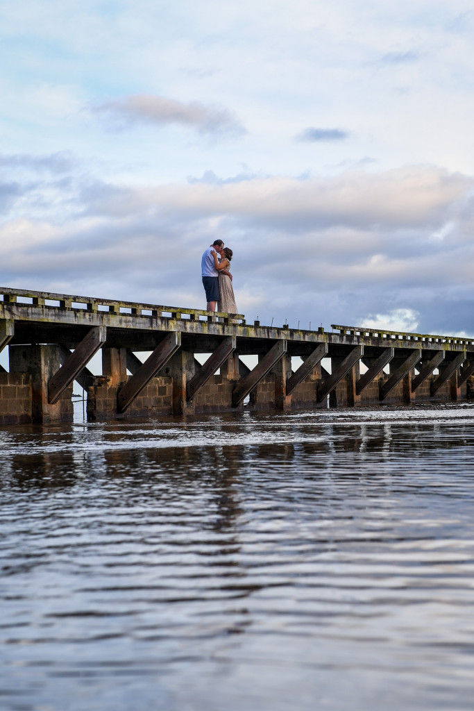 Bride and groom kiss on a bridge in the Pacific in Fiji