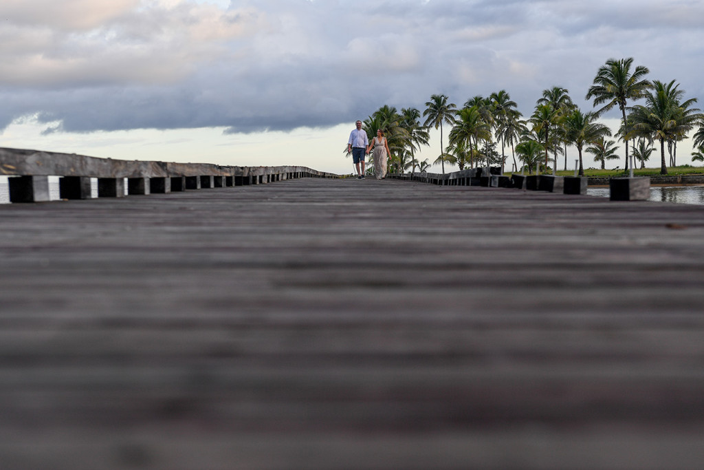 Bride and groom stroll on bridge against palm trees at Naviti Resort Fiji