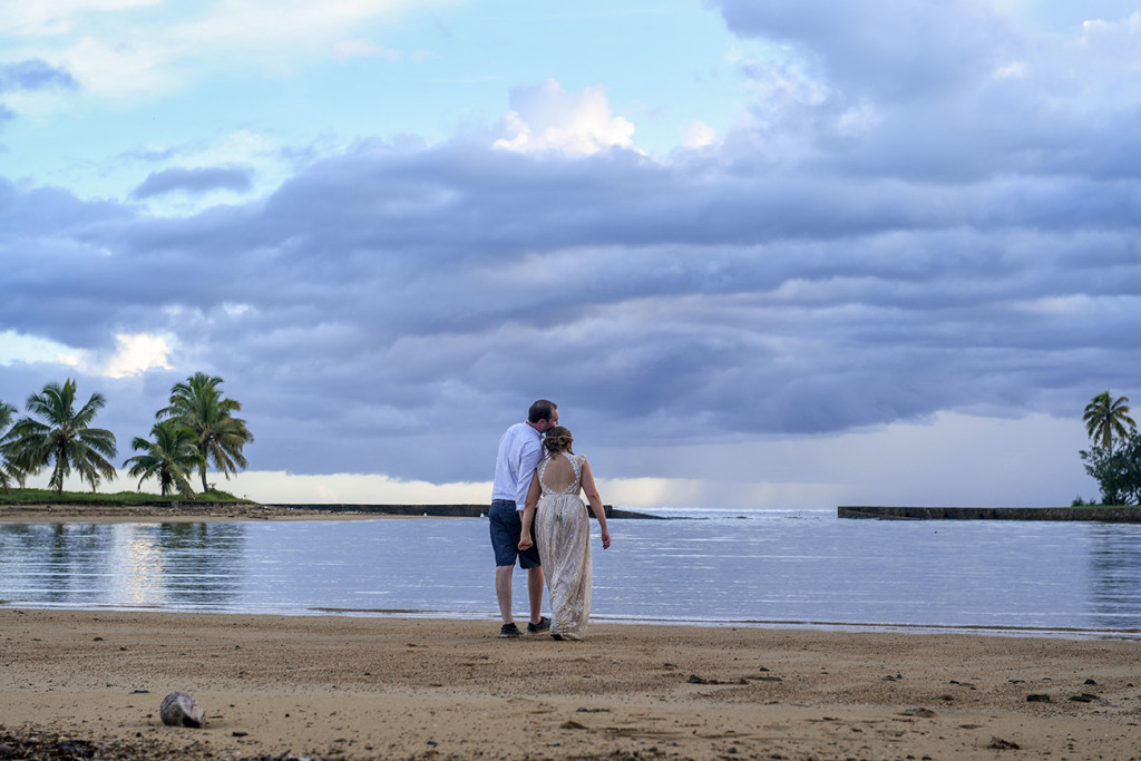A stroll against magnificently stormy sunset by the bride and groom