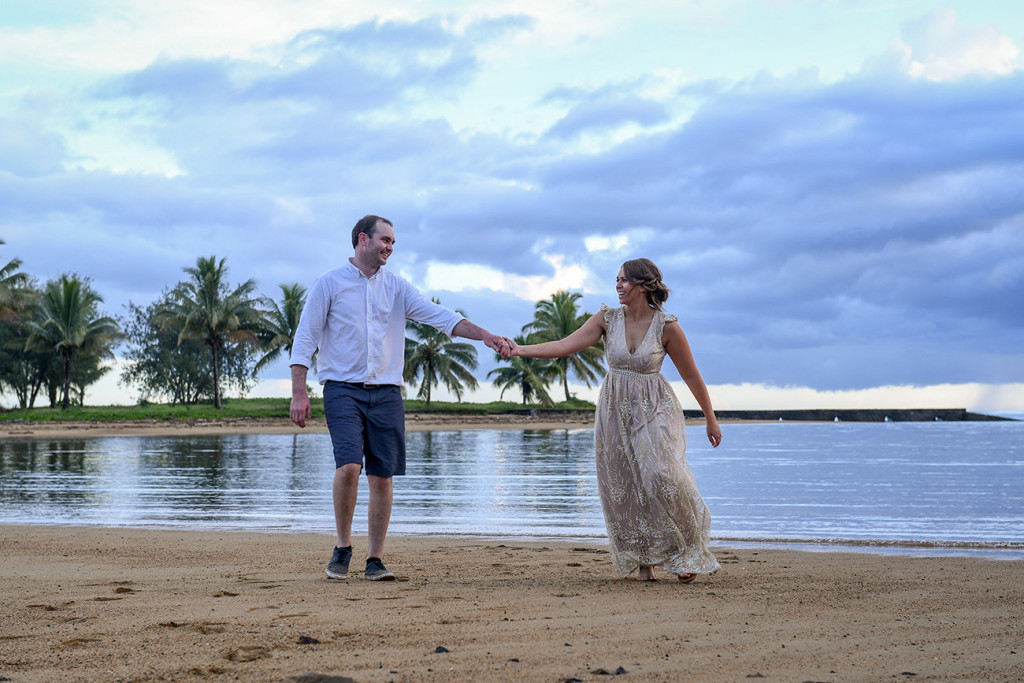Bride and groom play hand in hand against magnificent susnet at Naviti Fiji