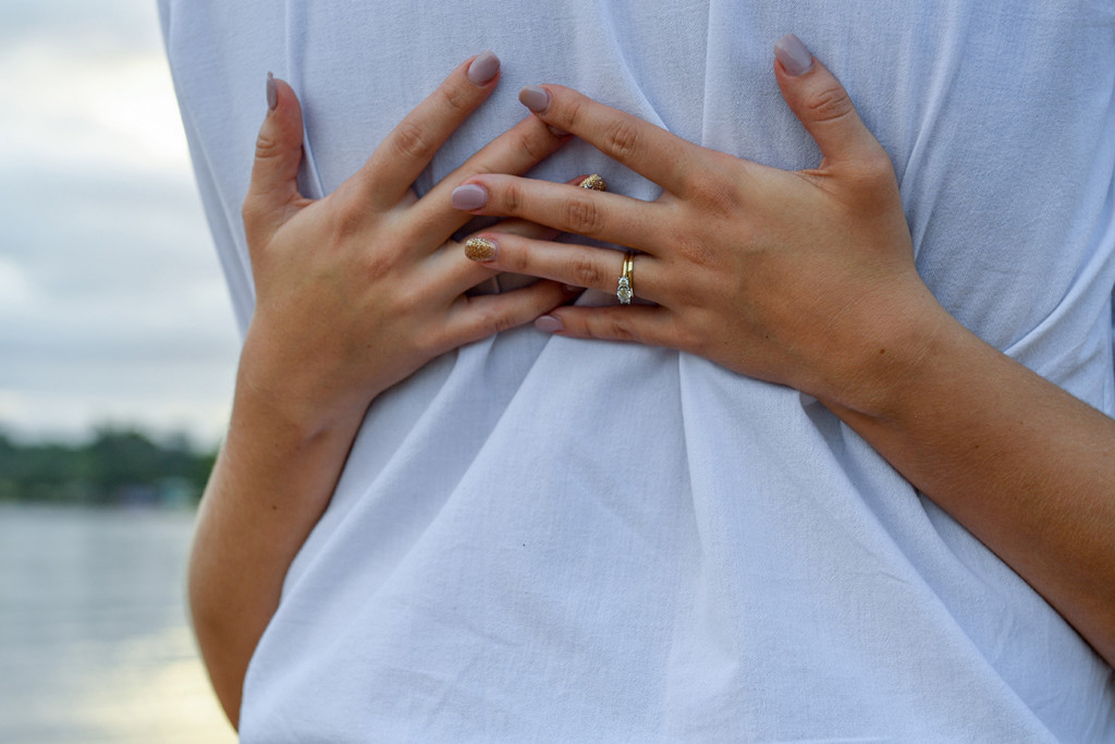 Closeup of bride's hands behind her groom's back
