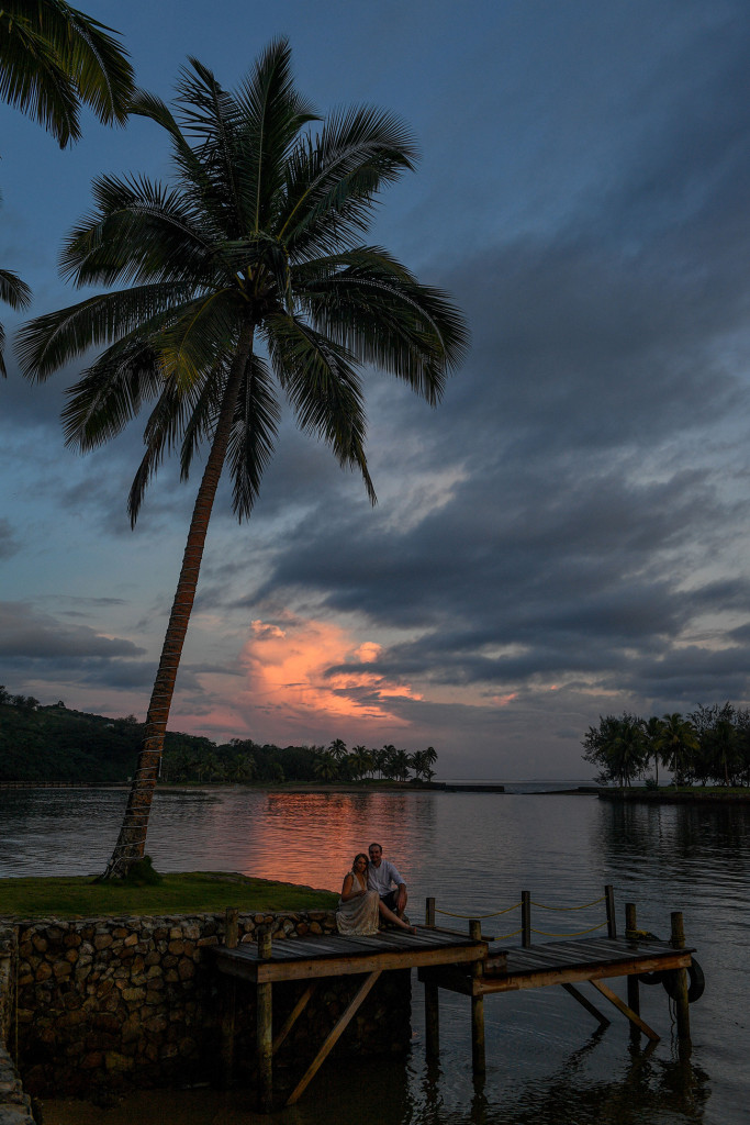Bride and groom seated on bridge against Lone palm tree in fiery sunset