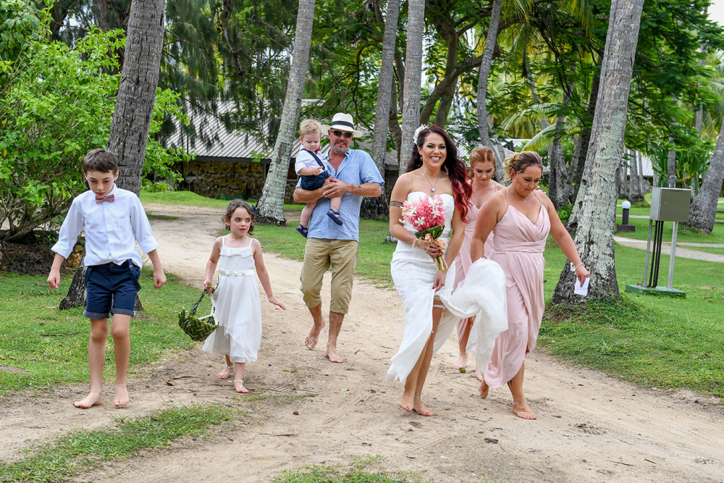 The bride, bridesmaids and flower girls and boys walk in the sand toward the ceremony.