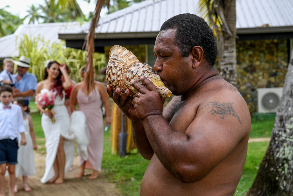 A traditional Fiji warrior blows into a shell during the wedding ceremony