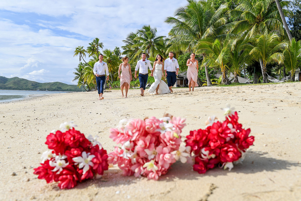 Ginger flower bouquet in sharp focus as the bridal party walk on the beach in the background?