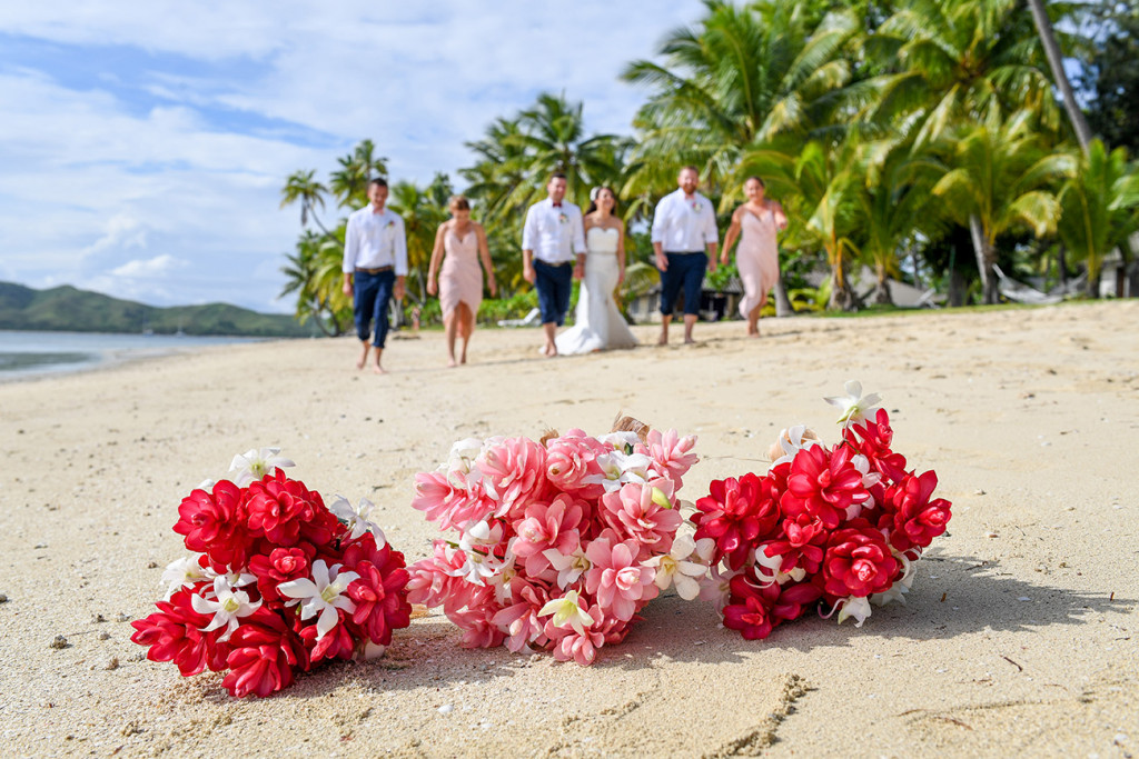 Ginger flower bouquet in soft focus as the bridal party walk on the beach in the background?