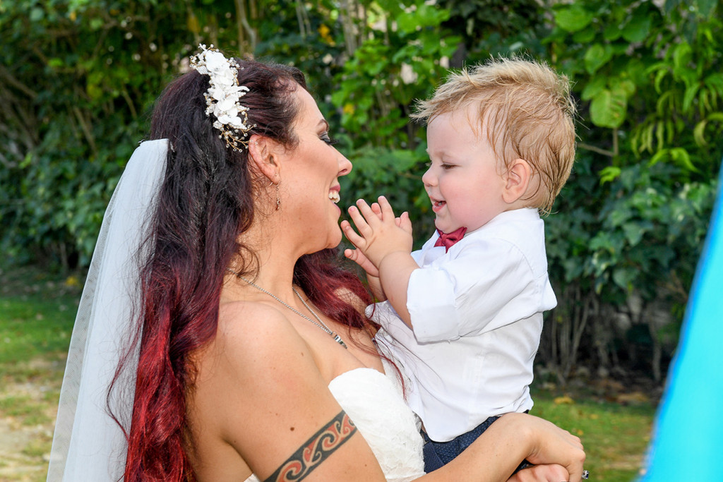 Bride laughs with her son on her wedding ceremony
