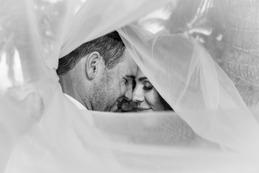 Under the veil: Monochrome image of the Bride and groom share an intimate moment wrapped in the bride's veil