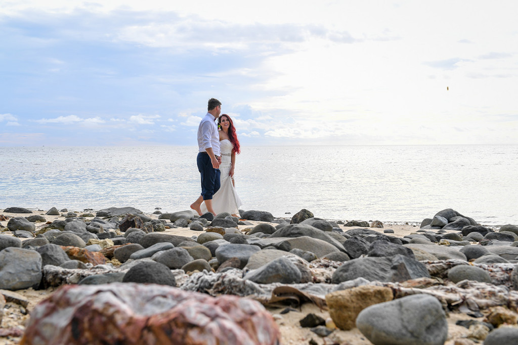 The married couple stand on rocky beach at the Plantation Island Resort