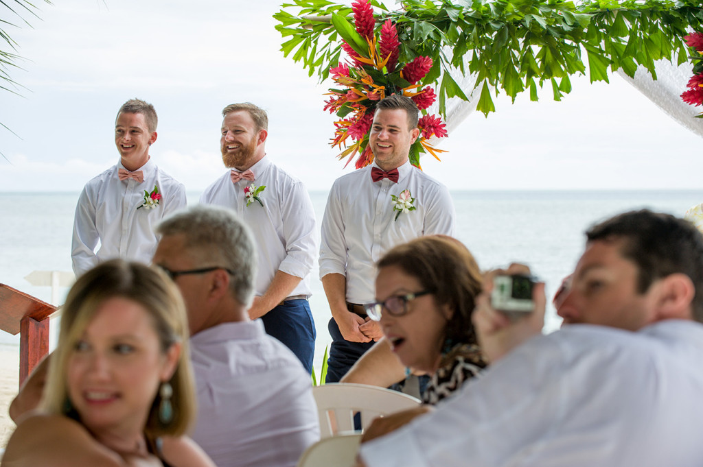 Groom and groomsmen smile as they watch the bride walk down the aisle