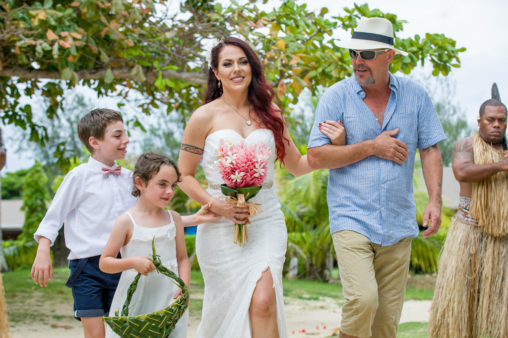 A happy bride walks down the aisle in her father's arm