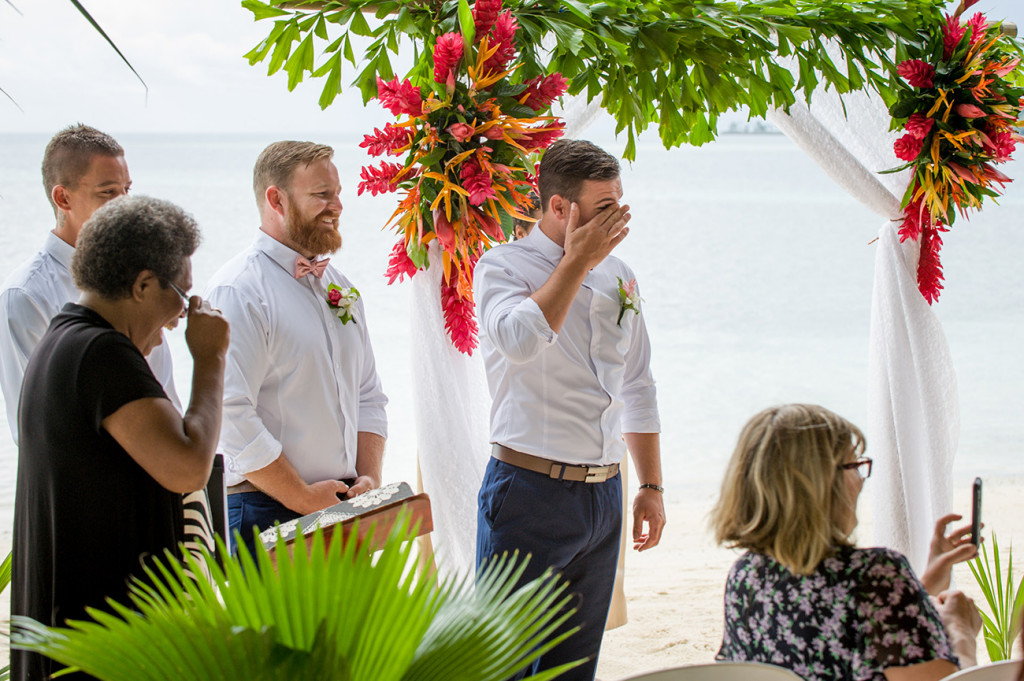 The groom wipes a tear as he watches his bride walk down the aisle