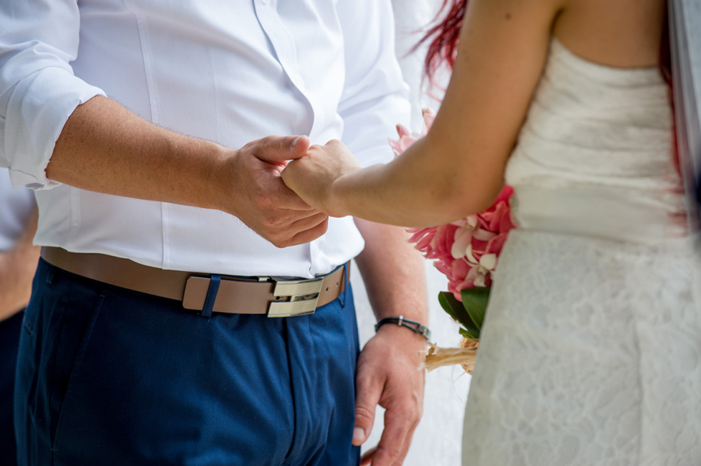Closeup of the bride and groom holding hands at the ceremony