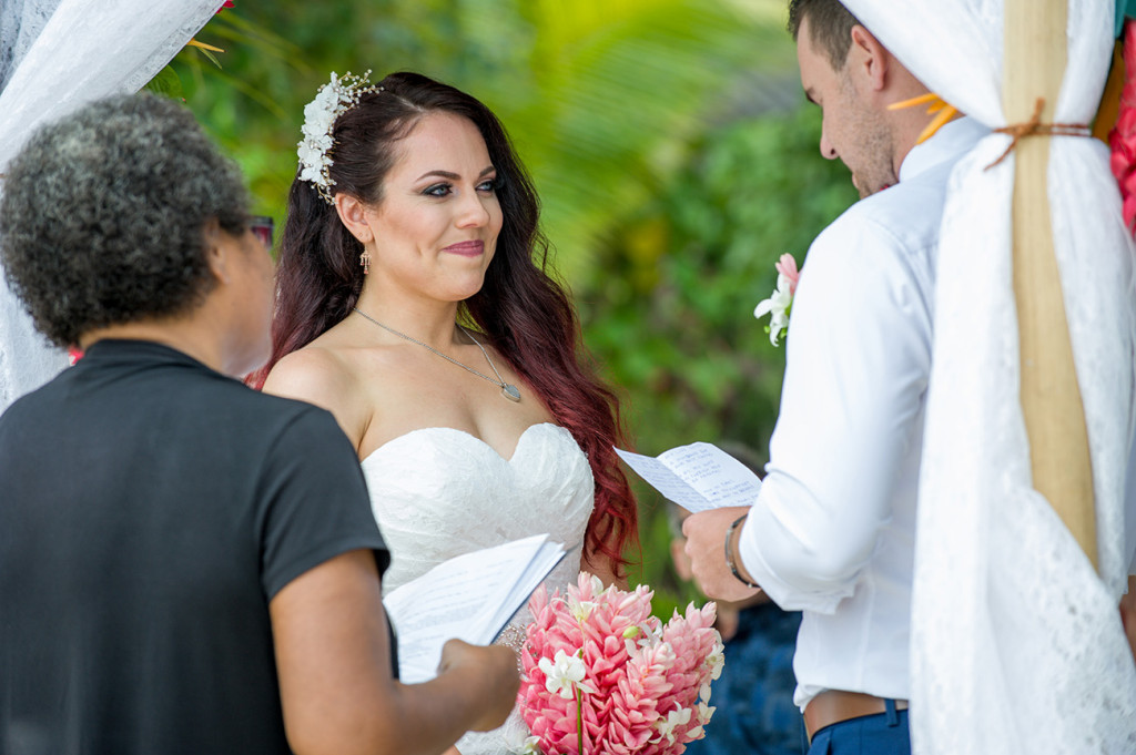 A blushing bride smiles as her groom reads the vows