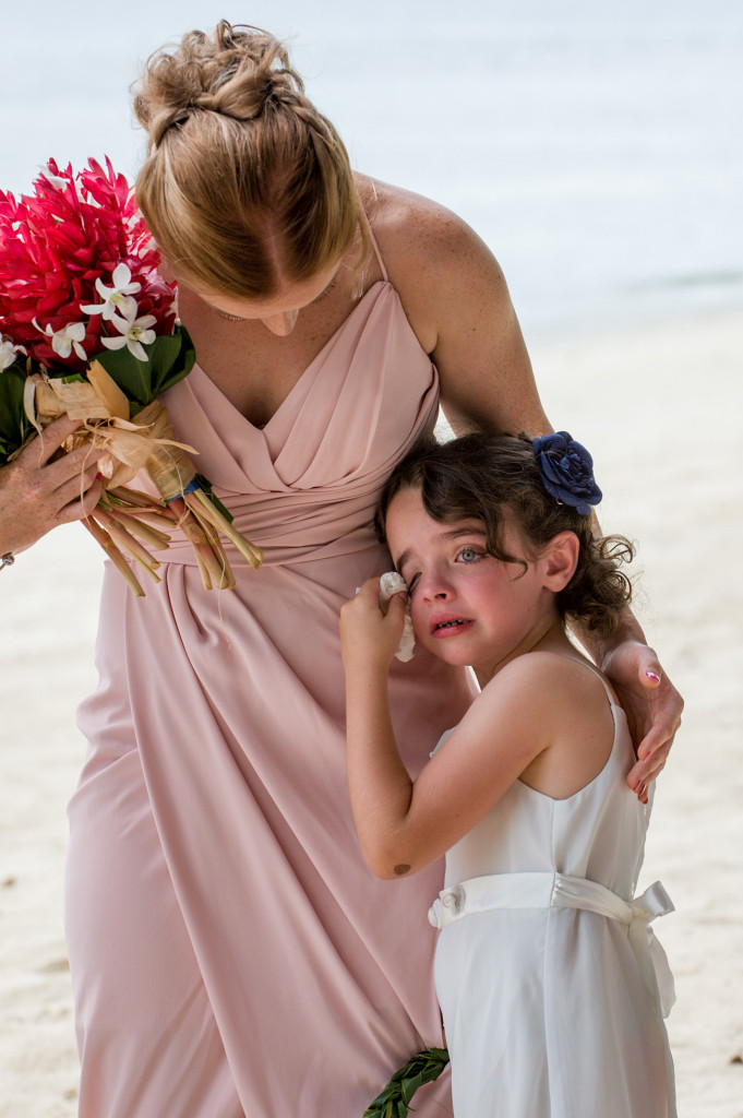 The flower girl wipes tears as she watches her parents marry