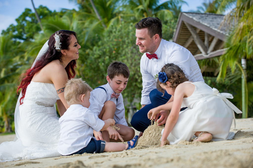 Bride groom and their children build sand castles on the beach