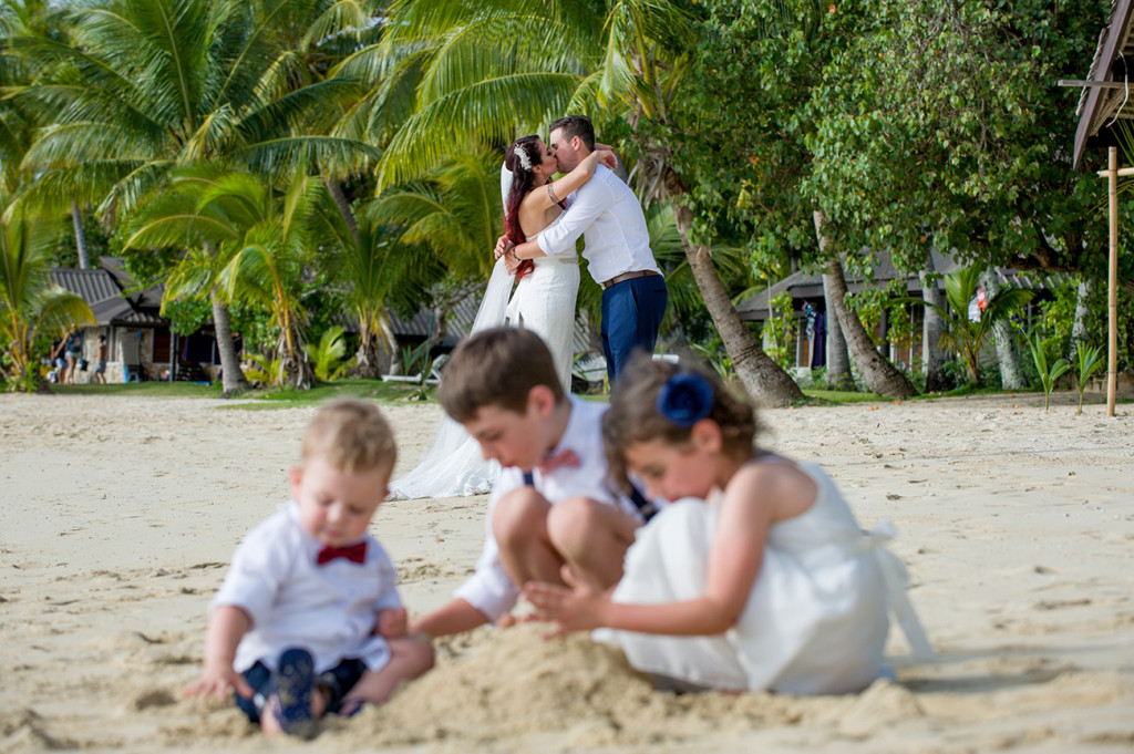 The children play in the foreground as the married couple kiss in the background