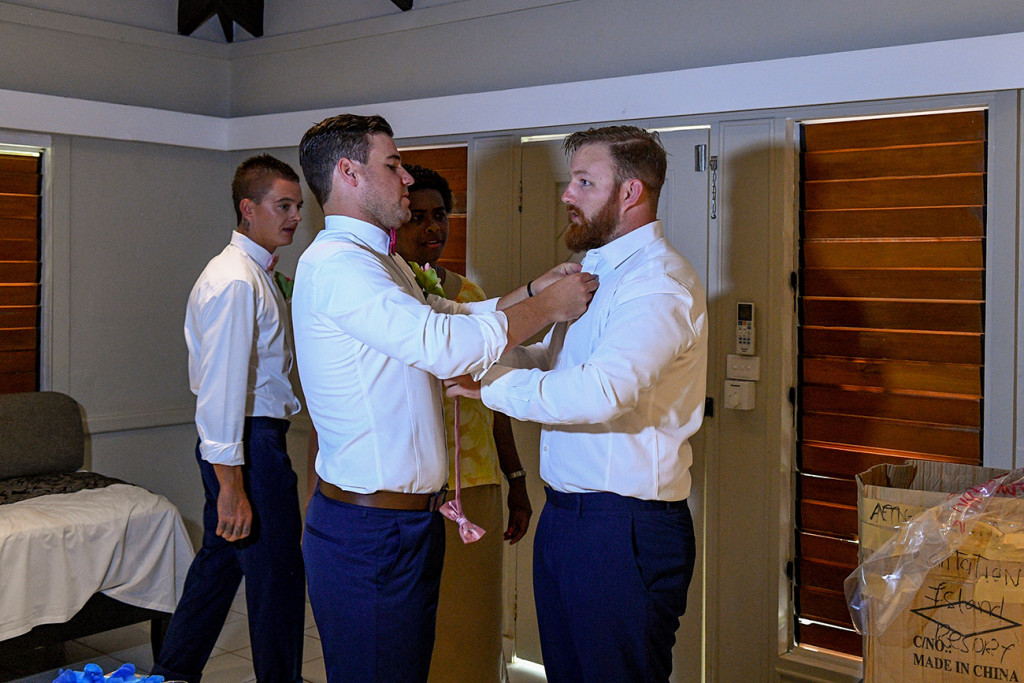 Groomsman buttons the groom's collar with suits made from Tarocash
