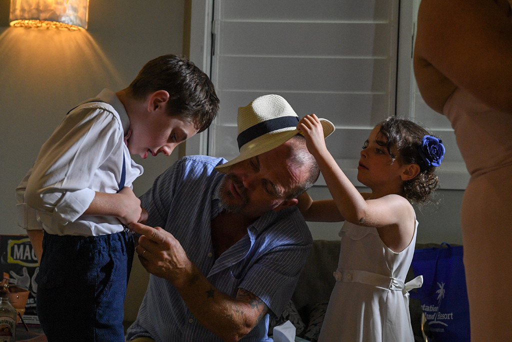Grandfather helps his grandson put on his suspenders