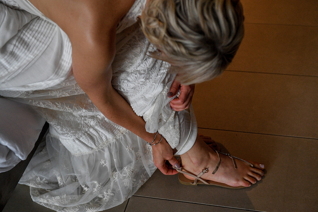 Bride straps her beige wedding sandals by siren shoes