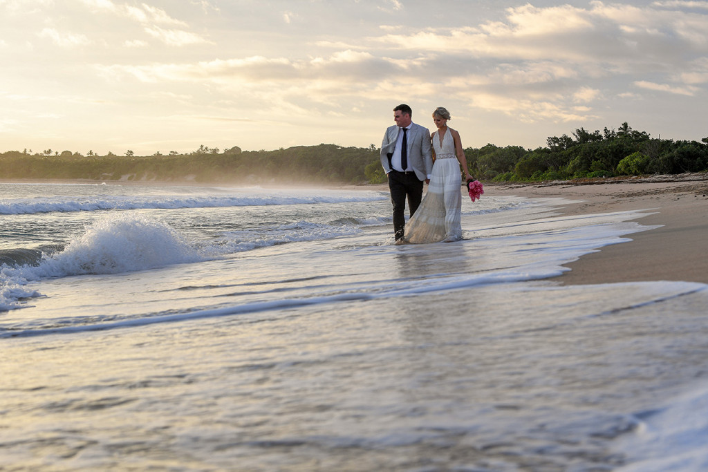 Newly wed bride and groom stroll hand in hand on the Fiji Coral Coast on their elopement