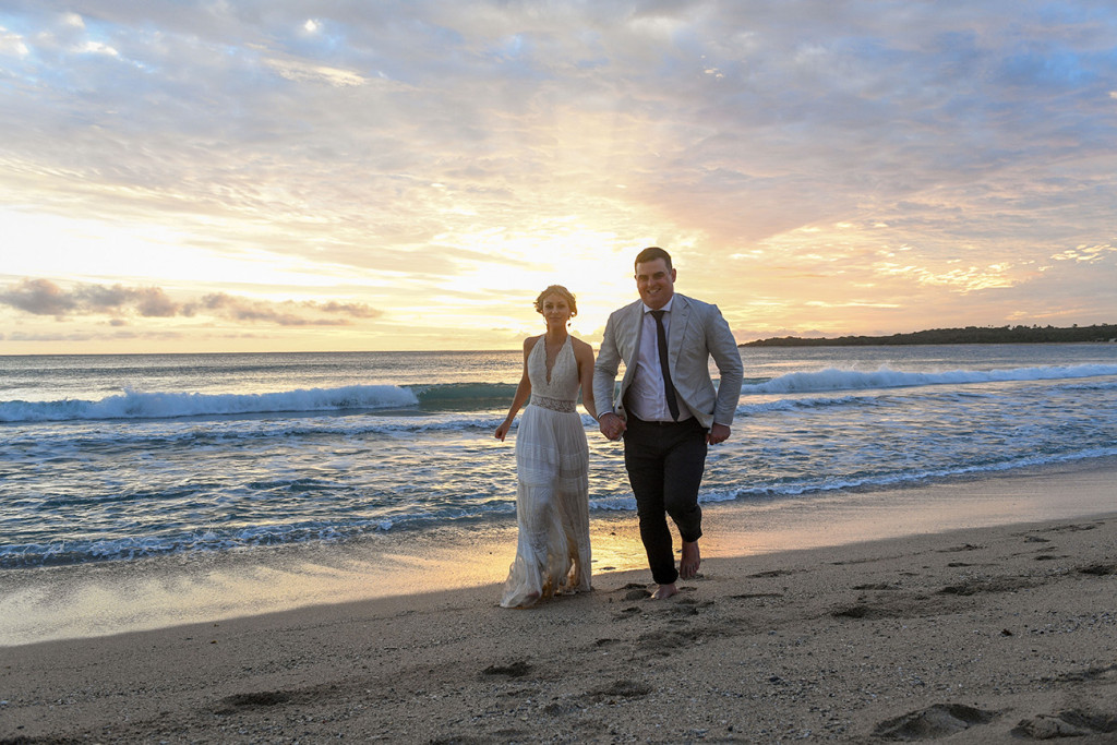 Newly eloped man and wife run on the beach against the sunset at Yatule Resort Fiji