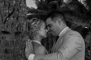 Monochrome candid image of the bride and groom intimate against a palm tree