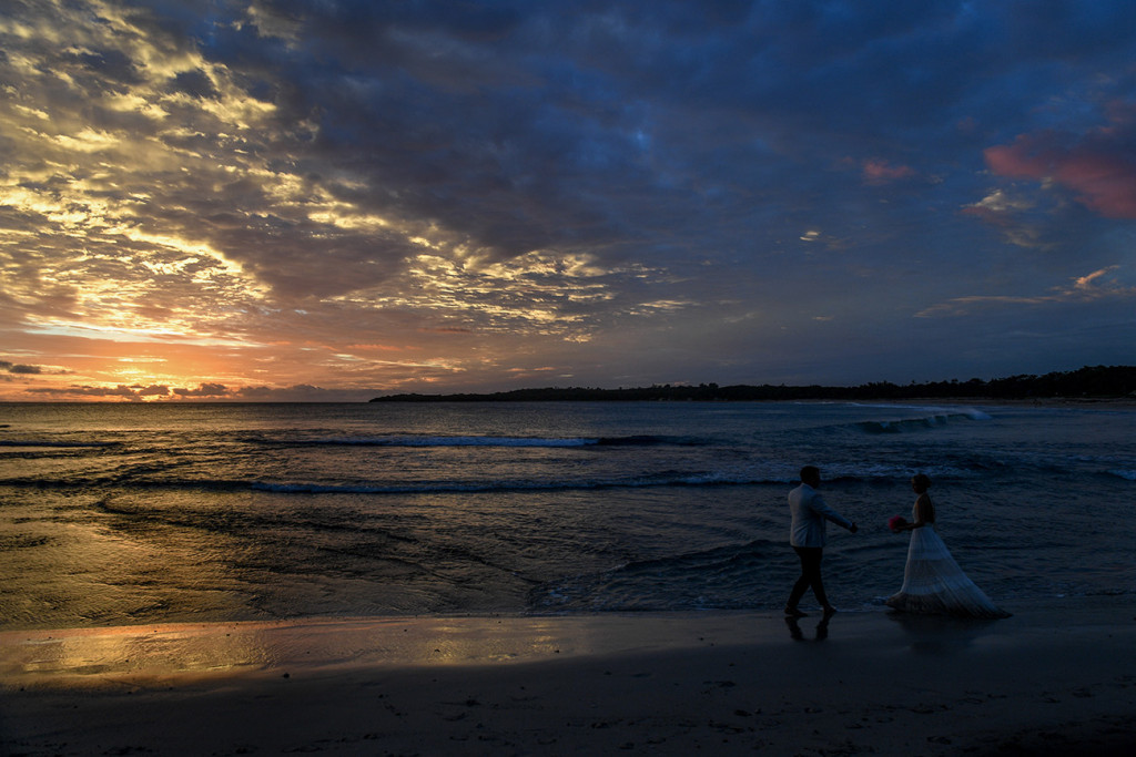 Bride and groom dance on the beach against the Blue and orange sunset at the Yatule Resort Fiji